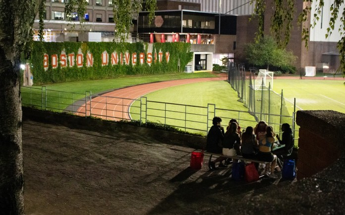 Boston University students spend Thursday evening in small groups outside their dorms at Nickerson Field.