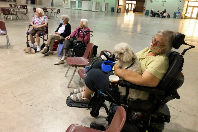 Patricia Fouts, 73, sits with her dog Murphy and other evacuated residents of the Marian Estates senior living home in an evacuation center at the Oregon State Fairgrounds on Tuesday.