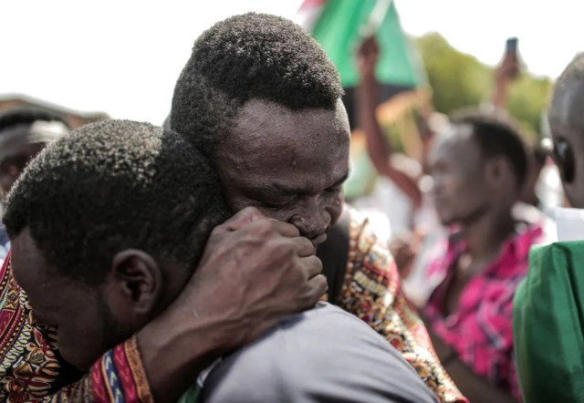 Sudanese men embrace outside the Friendship Hall in the capital Khartoum where generals and protest leaders signed a historic transitional constitution meant to pave the way for civilian rule in Sudan, on August 17, 2019. - The constitutional declaration formalizes the creation of a transition administration that will be guided by an 11-member sovereign council, comprised of six civilians and five military figures.