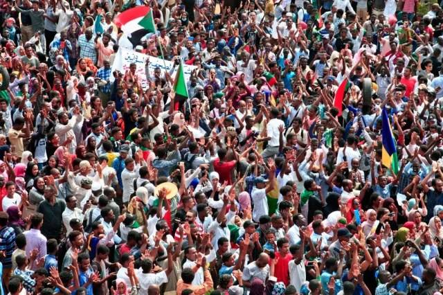 People wave Sudanese national flags as they rally at a mass demonstration near the presidential palace in the capital Khartoum on September 12, 2019, calling for the appointment of a new permanent chief of judiciary and prosecutor general.