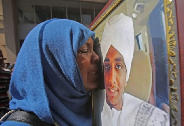 A Sudanese protester cries next to a photo of a relative during a protest asking for the extradition of ousted former president Omar al-Bashir to the International Criminal Court in the capital Khartoum on September 19, 2019.