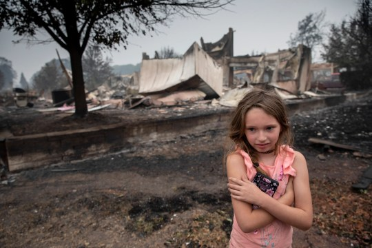 Ellie Owens, 8, from Grants Pass, Ore., looks at fire damage Friday, Sept. 11, 2020, as destructive wildfires devastate the region in Talent, Ore.