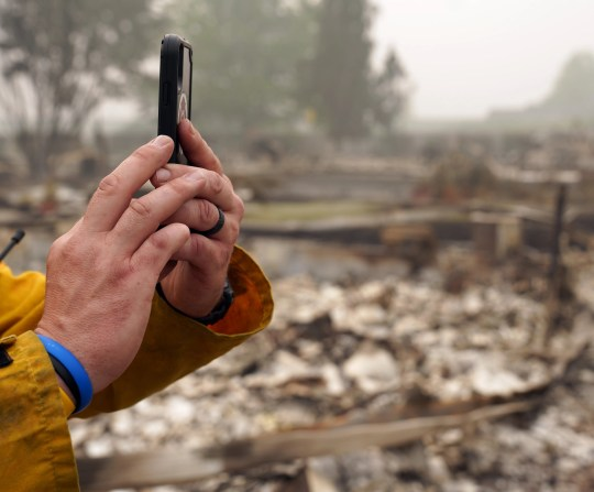 A firefighter takes a picture of a relative's destroyed home near Medford, Ore., following the passage of the Almeda fire.