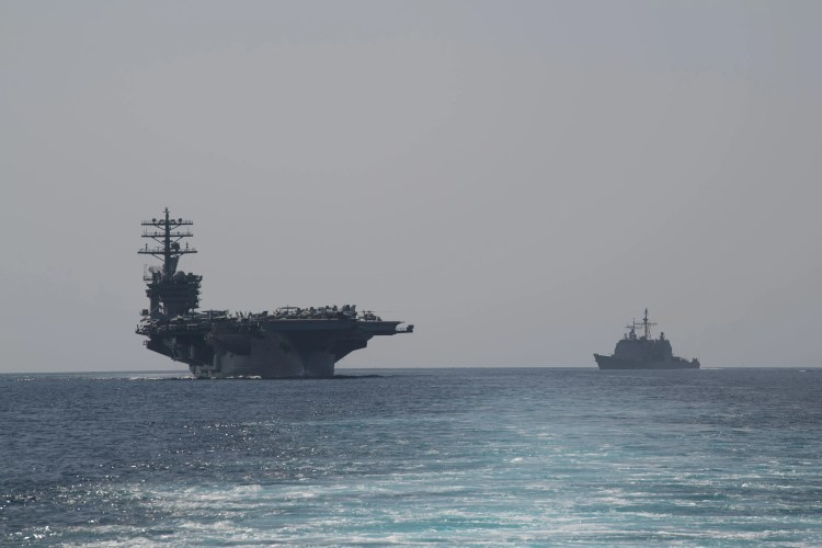 The aircraft carrier USS Nimitz, left, and the guided-missile cruiser USS Philippine Sea steam in formation during a Strait of Hormuz transit back on Sept. 18. On Friday, the Nimitz and its strike group was ordered back to the Persian Gulf.