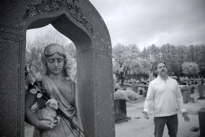 """Ronny Le Blanc of Leominster has been featured on Animal Planet's """"Finding Bigfoot"""" and """"In Search of Monsters"""" and the Travel Channel's """"Expedition Bigfoot."""" Le Blanc is pictured in St. Leo's cemetery, where a couple reportedly had a UFO encounter late one night. It was shot using a black and white, infra-red camera. The photographer cannot account for the disc-shaped object above the trees at right."""