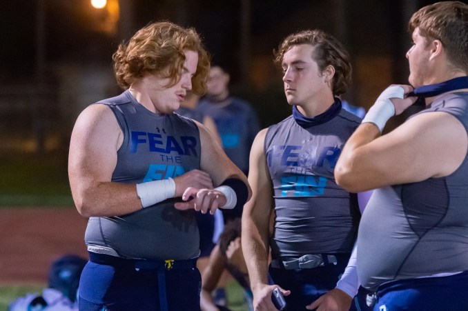 Peyton Todd (L) and Noah Simon (M) talking with teammate during pregame as the Southside Sharks take on Lafayette High. Friday, Nov. 6, 2020.