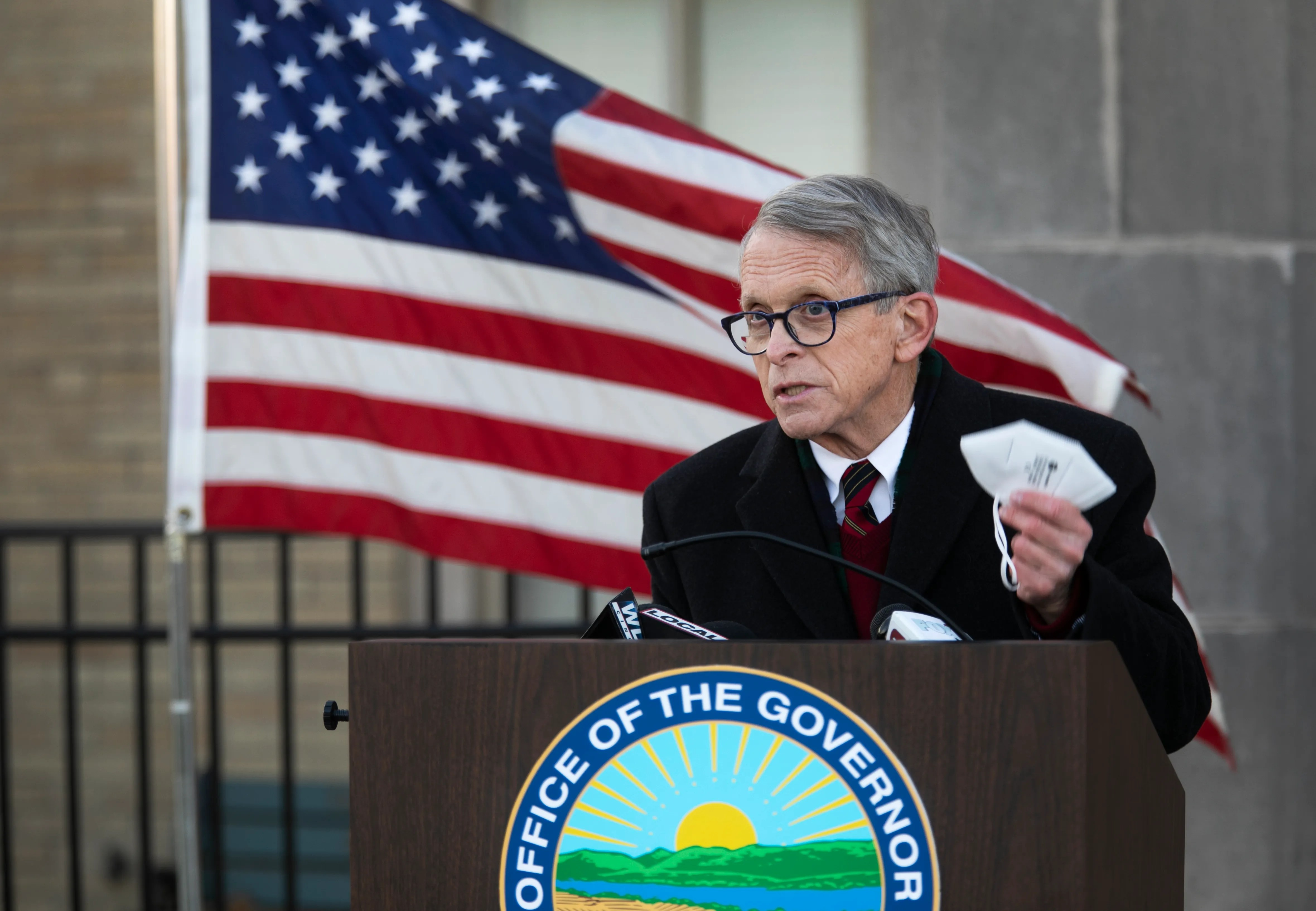 Gov. Mike DeWine holds his masks up during a press conference at Lunken Airport, Wednesday, Nov. 18, 2020. DeWine traveled across the state to enforce the curfew and the importance of masks and social distancing during the coronavirus pandemic.
