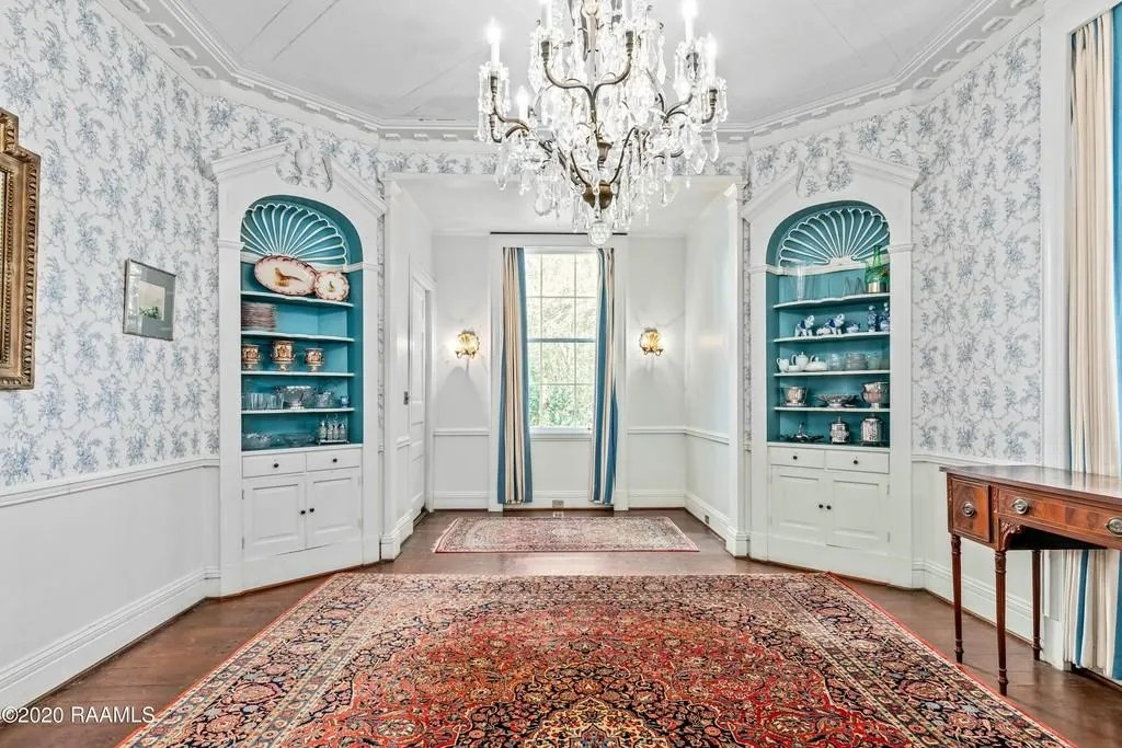 The crisp white foyer has stairs that lead to the second floor, and doors that offer glimpses into the colorful, wallpapered living areas. One area has built-ins with turquoise backgrounds and plenty of natural lighting.   Originally built in 1935, this Abbeville mansion is anything but your average historical Acadian mansion with an elevator, sauna,cabana, rose garden andwell on the property.