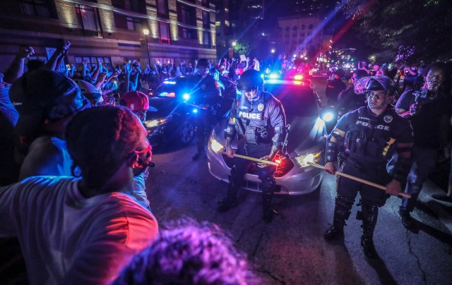 Police move protesters back as they try to move their patrol cars west on Main Street in front of the KFC Yum! Center in Louisville, Kentucky, on May 28, 2020 — part of a wave of demonstrations that followed the deaths of Breonna Taylor and George Floyd.