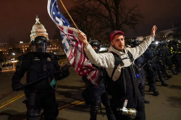 A police line moves a protestor outside of the Capitol, Wednesday night, Jan. 6, 2021, after a day of rioting protesters.