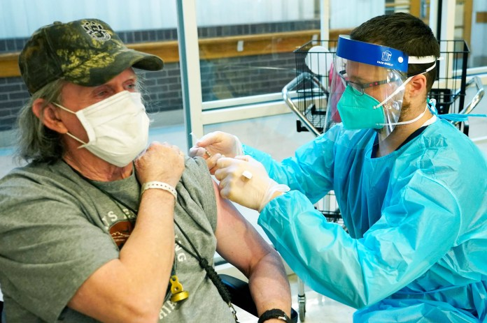 James Hill, 69, who served separate stints in the Army and Navy, left, pulls up his sleeve as Brent Myers, a CVS pharmacist, administers the Pfizer COVID-19 vaccine at the Mississippi State Veterans Home in Jackson on Jan. 9. Hill was among the first residents to receive the vaccine.