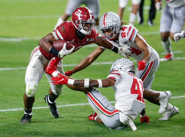 Alabama running back Najee Harris (22) is tackled by Ohio State safety Josh Proctor (41) and cornerback Shaun Wade during the College Football Playoff national championship game at Hard Rock Stadium in Miami Gardens, Fla.