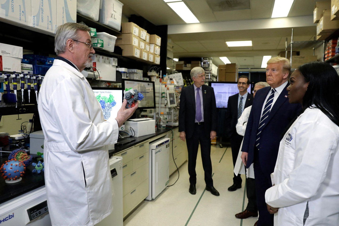 President Donald Trump tours the NIH's Health Vaccine Research Center on March 3, 2020 with Barney Graham, left, and Kizzmekia Corbett, right.