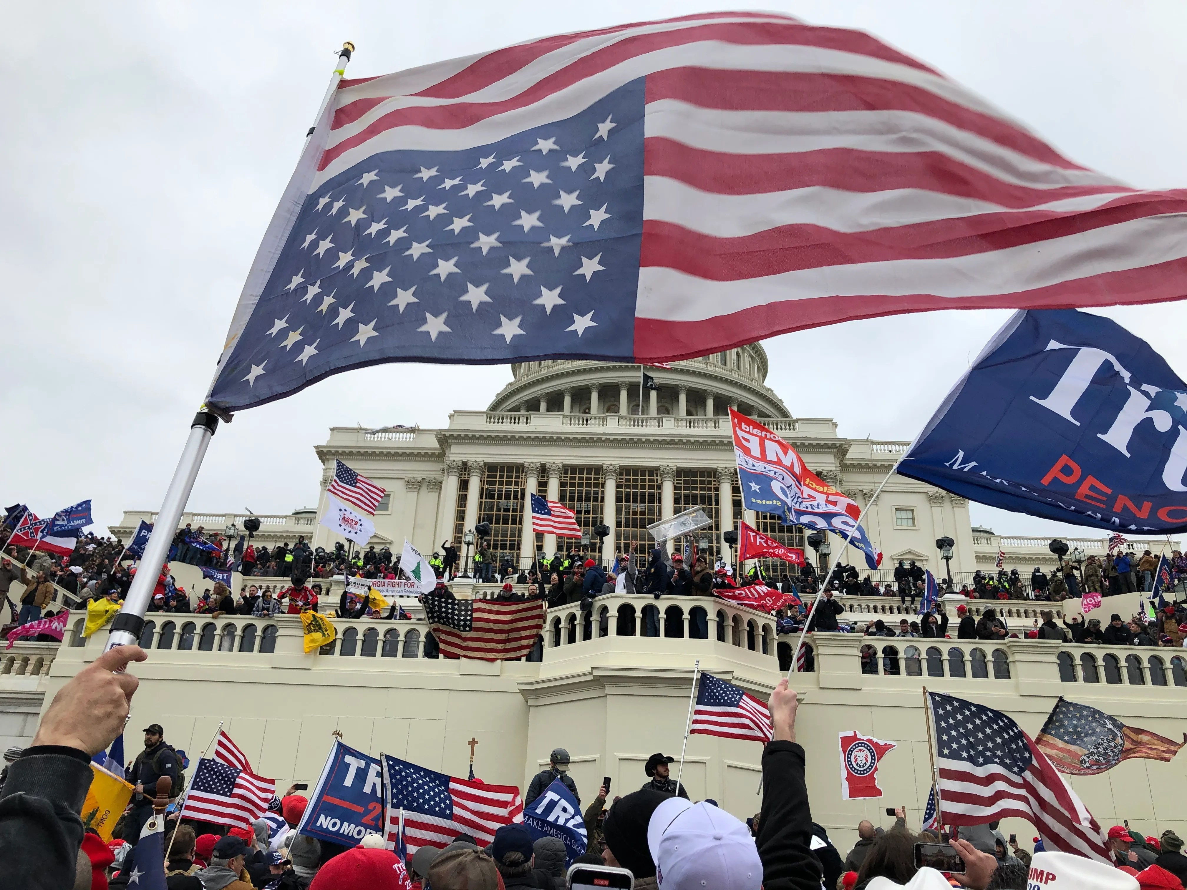 Pro-Trump rioters stand on the West front of the U.S. Capitol building during the Jan. 6, 2021 insurrection.
