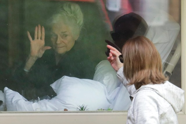 Judie Shape, left, waves to her daughter, Lori Spencer, through a window on March 11, 2020, after the Life Care Center in Kirkland, Wash., near Seattle, had stopped in-person visits.