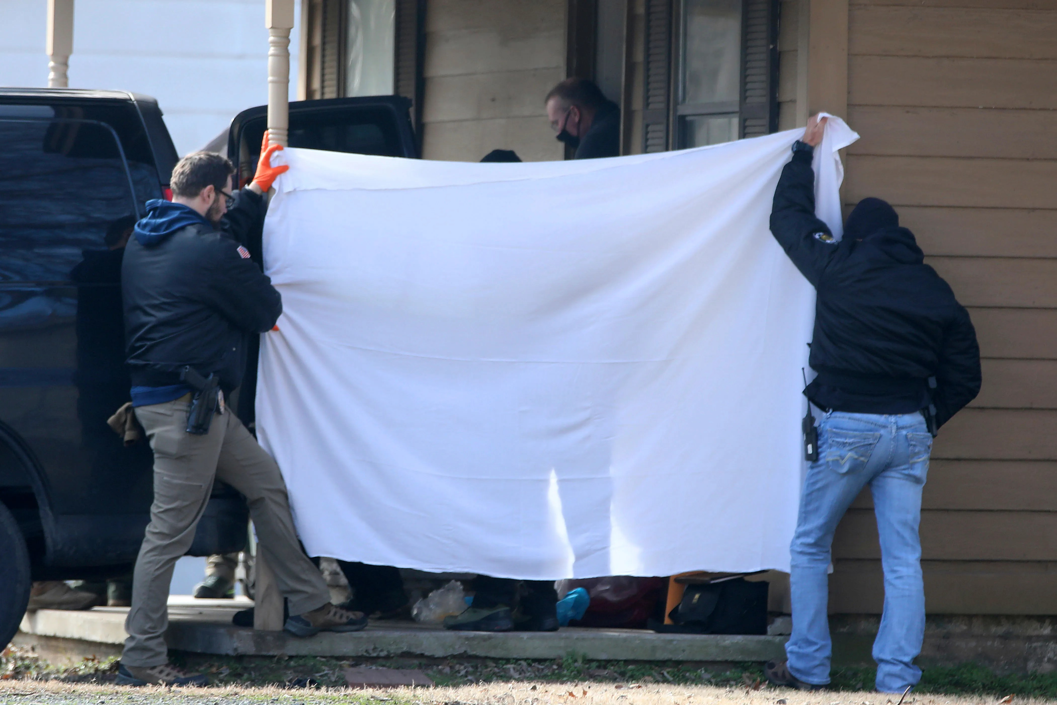 Investigators block the public's view as bodies are removed from the scene of a shooting on Tuesday, Feb. 2, 2021 in Muskogee, Okla.