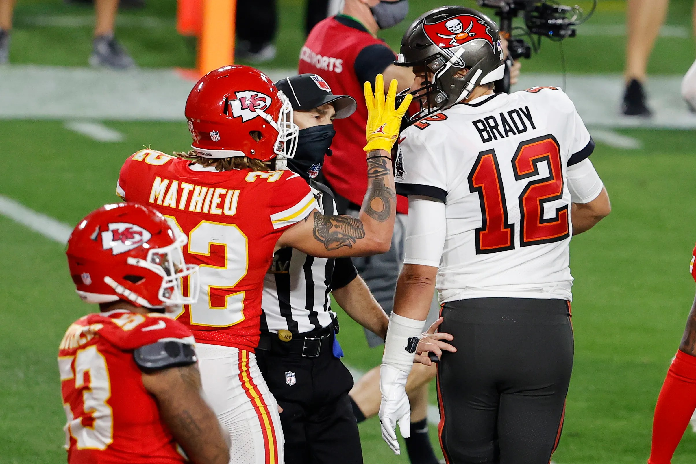 A NFL official moves in to separate Tampa Bay Buccaneers quarterback Tom Brady (12) and Kansas City Chiefs strong safety Tyrann Mathieu (32) during the second quarter of Super Bowl LV at Raymond James Stadium.