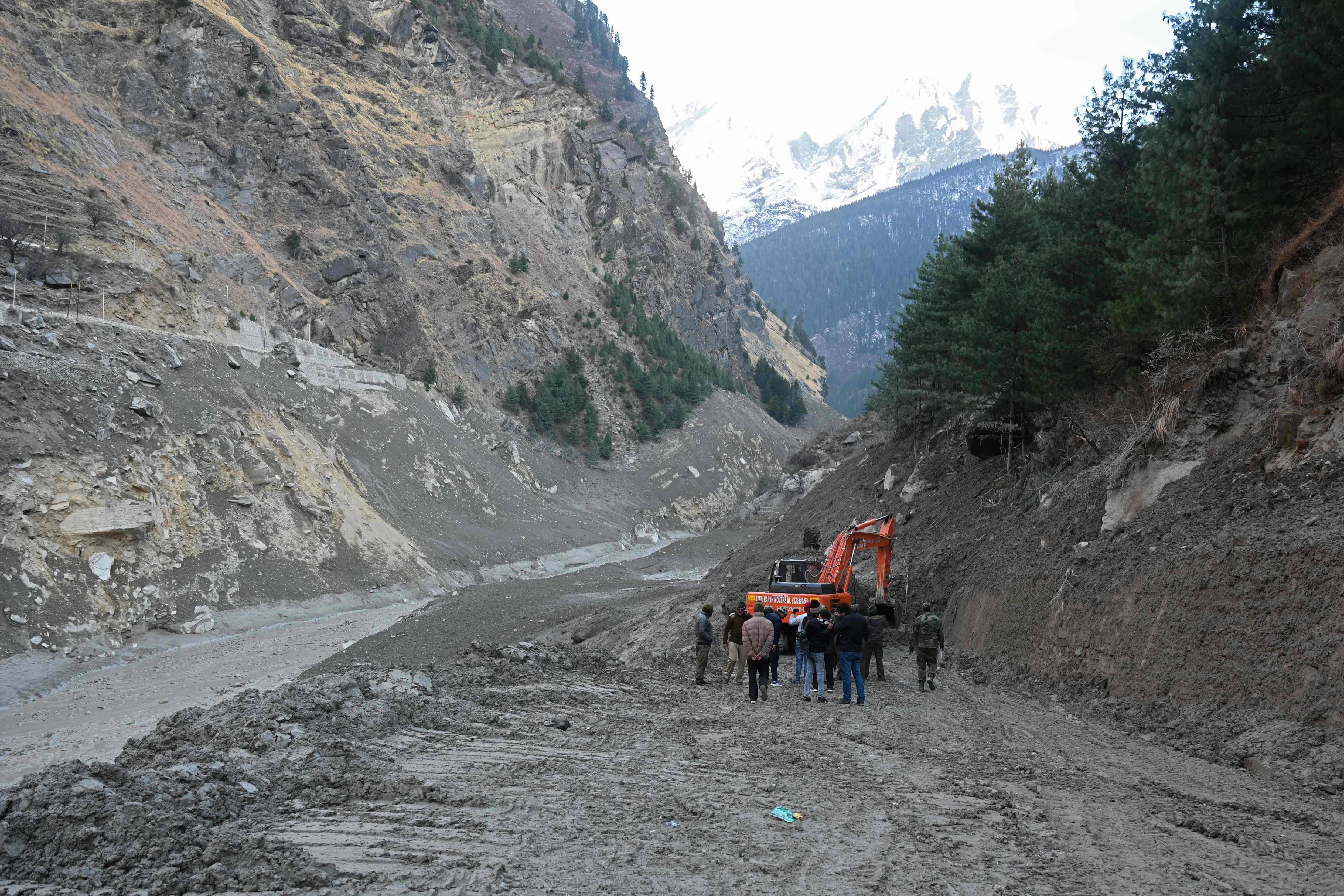 An excavator clears a road leading to the destroyed Raini bridge in the Chamoli district of Uttarakhand, India, on Feb. 8, 2021, after it was washed away by a flash flood caused by a glacier burst a day earlier.