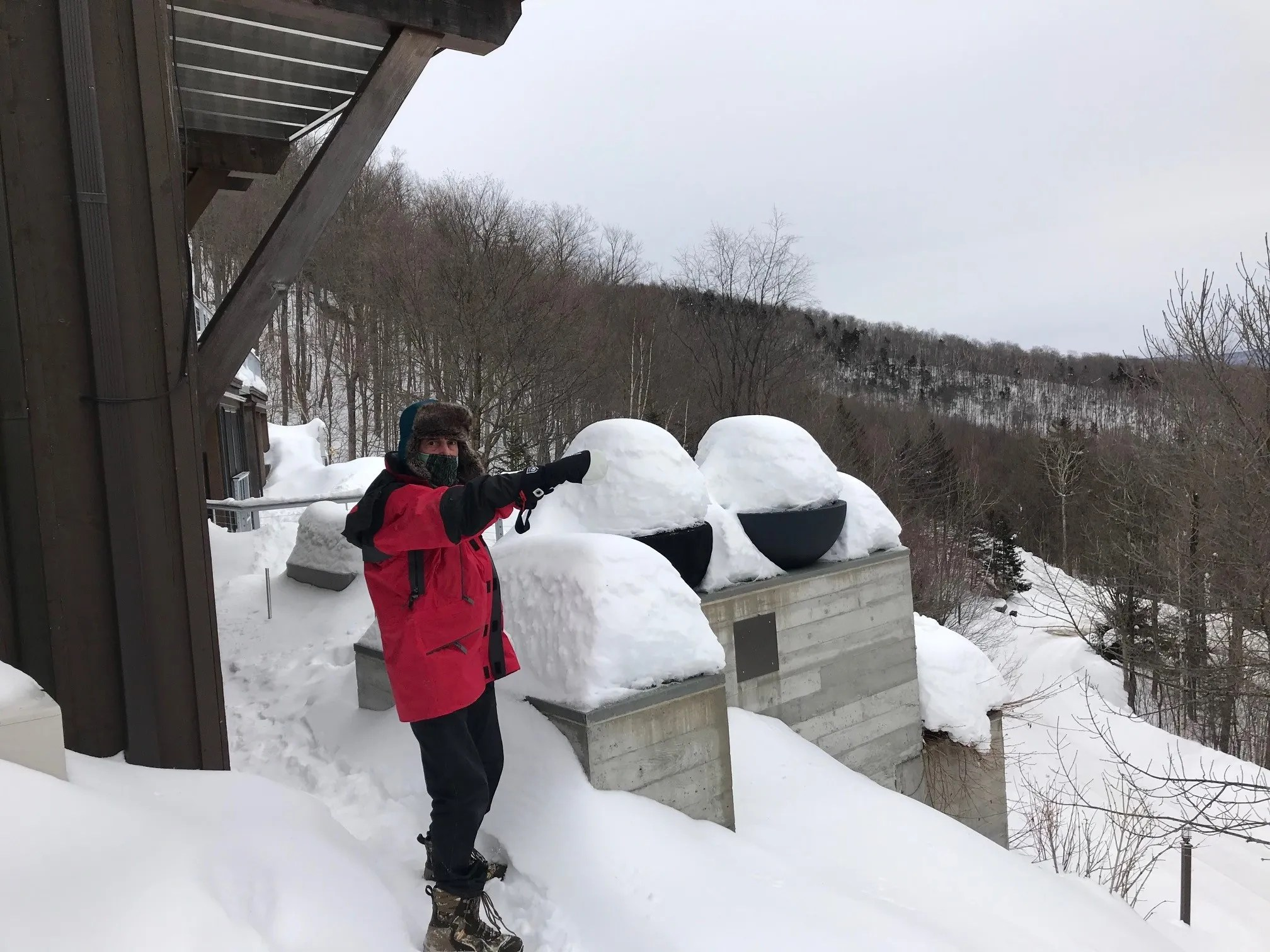 Mike Krancer shows another nearby house from his perch atop Bull Moose Ridge Road in Stowe, Vt. On February 18, 2021.
