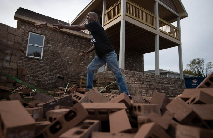 Sam Brown tosses bricks at his home on Nov. 5, 2020 in Nashville, Tenn. Brown decided to serve as his own contractor to rebuild his demolished home after a tornado ripped through the neighborhood in March 2020.