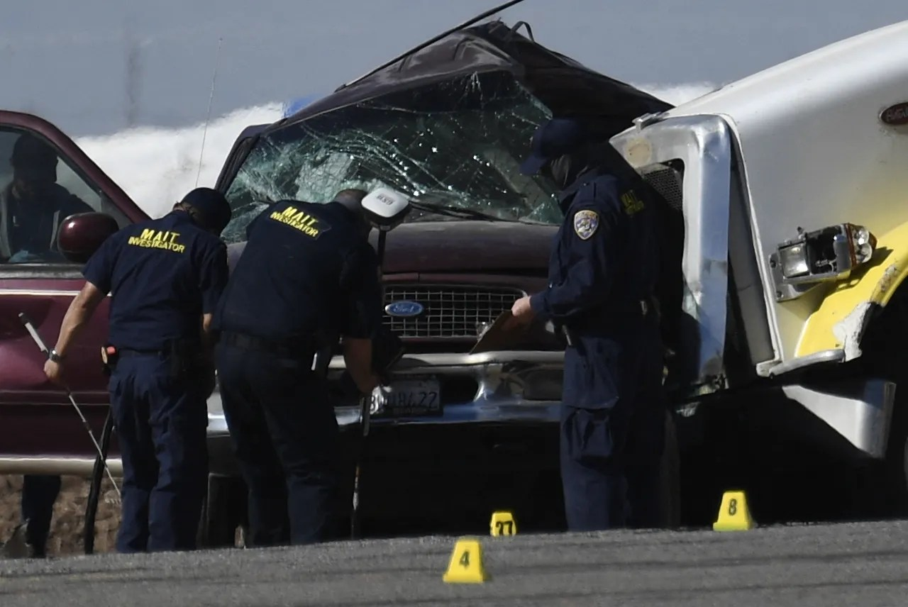 Investigators look over the scene of a crash between an SUV and a semi-truck full of gravel near Holtville, California on March 2, 2021.