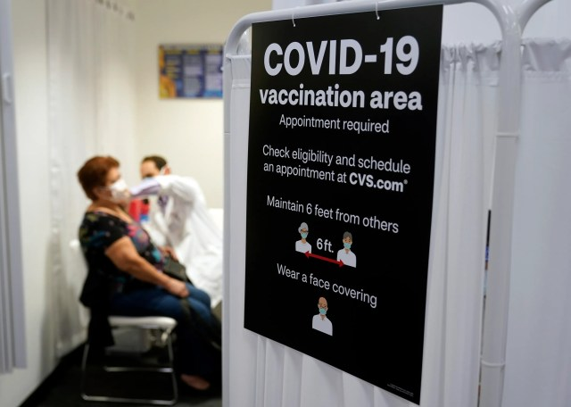 A patient receives a shot of the Moderna COVID-19 vaccine at a CVS Pharmacy branch in Los Angeles.