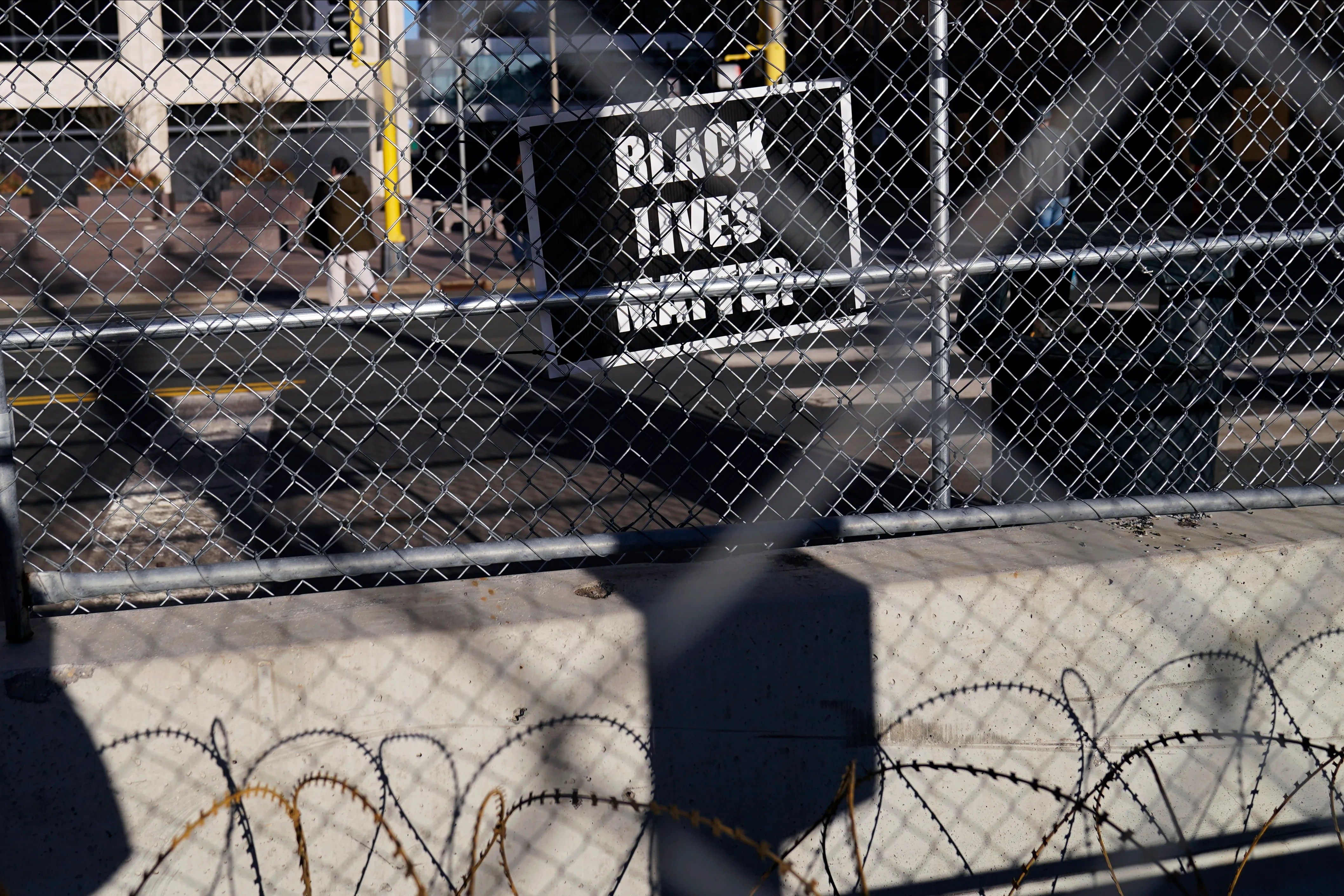 A lone Black Lives Matter sign hangs on the fence surrounding the Hennepin County Government Center, Thursday, March 18, 2021, in Minneapolis where the trial for former Minneapolis police officer Derek Chauvin continues with jury selection. Chauvin is charged with murder in the death of George Floyd during an arrest last May in Minneapolis.
