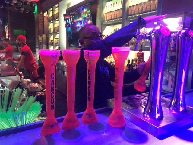 A bartender at Senor Frog's, a popular tourist spot in downtown Cancun, serves Dos Equis in 28-ounce souvenir cups.