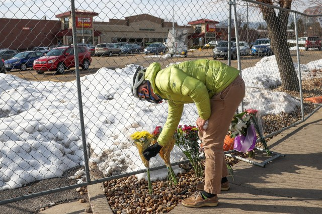 Rudy Kahsar lays flowers at a makeshift vigil outside a King Soopers grocery store in Boulder, Colo. on March 23, 2021 the day after multiple people were killed, including a police officer.