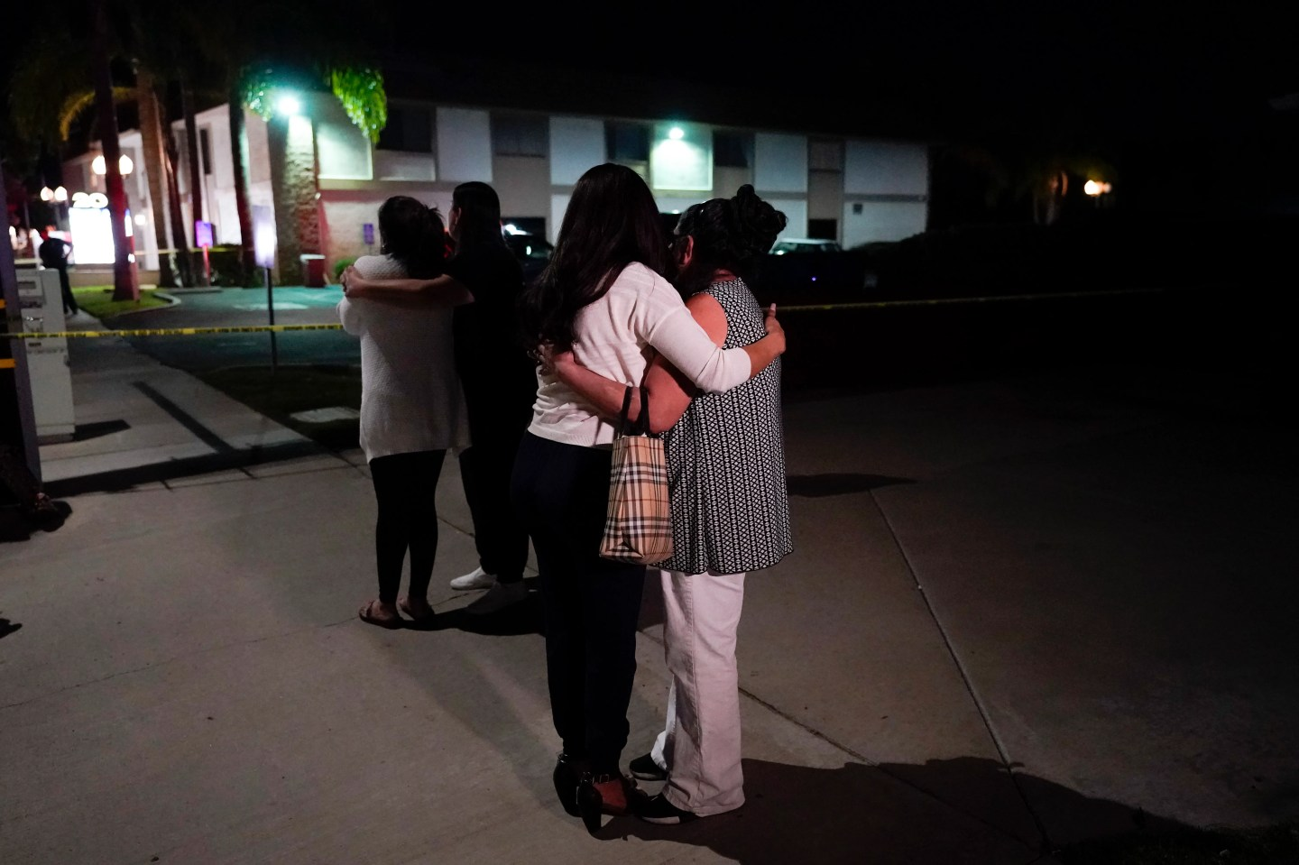 People are pictured comforting each other as they stand near a business building where a shooting occurred in Orange, California. Authorities say 4 people, including a child, died during the shooting late Wednesday.