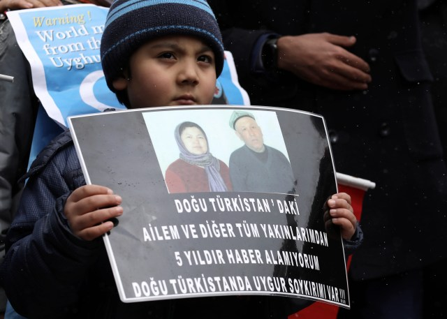"""A Uyghur boy holds a placard that reads: """"I cannot have any news from my family and relatives in Eastern Turkistan"""", during a protest near the Chinese embassy in Ankara, Turkey, on March 25."""