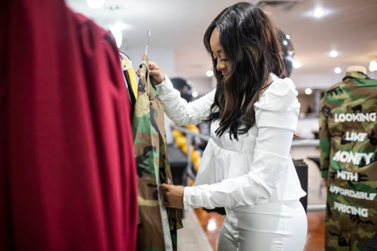 Renee Nesbitt, owner of Building Bosses Boutique arranged clothes on a rack at her pop-up shop on the west side of Detroit on March 13, 2021.