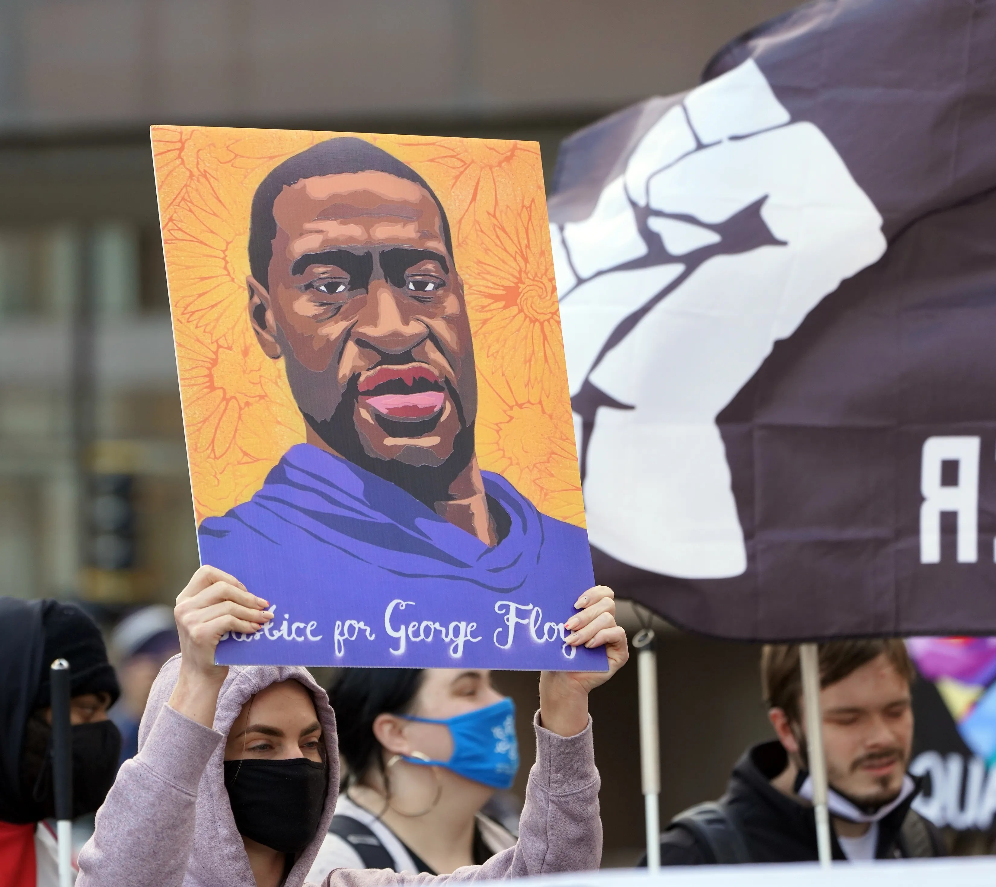 Vanessa Boerhave, 33, of Minneapolis, holds a sign bearing the image of George Floyd at a protest and march held to mark the first day of the trial against former Minneapolis police Officer Derek Chauvin, who is accused of killing Floyd, sparking a wave of protests and riots nationally.