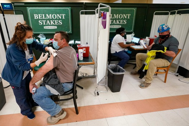A nurse (left) inoculates a metal worker on Wednesday with a dose of the COVID-19 Pfizer vaccine at a coronavirus vaccination site at Belmont Park in Elmont, New York.