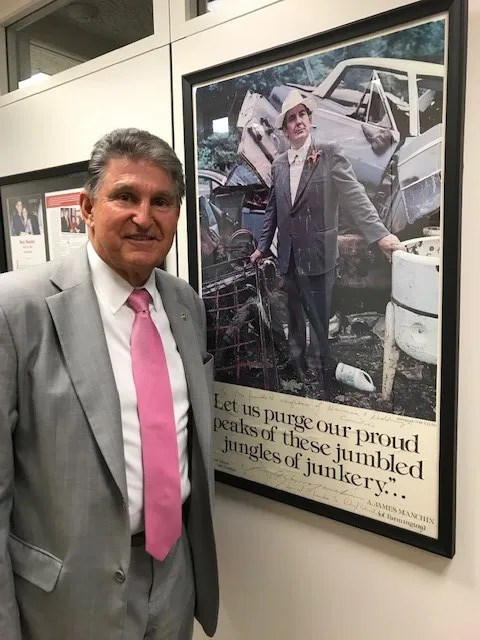 """Sen. Joe Manchin, D-W.Va., stands in his Capitol Hill office next to a framed poster of his flamboyant uncle A. James """"Jimmy"""" Manchin, who served as West Virginia secretary of State and helped inspire a young Joe Manchin to pursue public service."""