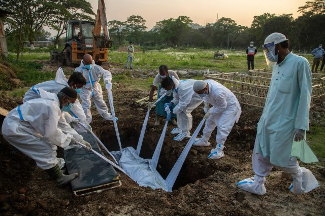 Relatives and municipal workers in protective gear bury the body of a person who died due to COVID-19 in Gauhati, India, Sunday, April 25, 2021.