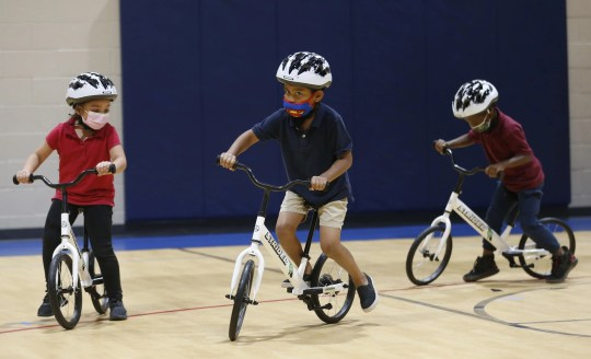Children make their loops around the gym in the donated bicycles during an All Kids Bike event at Scales Technology Academy in Tempe on May 6, 2021.