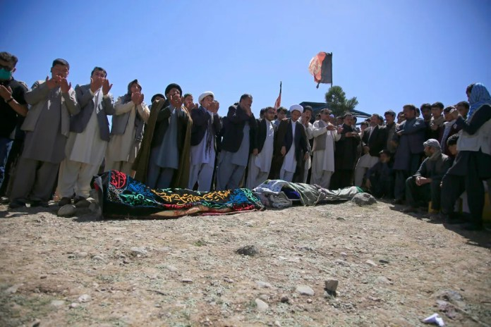 Afghans pray during the funeral of victims of deadly bombings on Saturday near a school, at a cemetery west of Kabul, Afghanistan, on May 9, 2021. The Interior Ministry said Sunday the death toll in the horrific bombing at the entrance to a girls' school in the Afghan capital has soared to some 50 people, many of them pupils between 11 and 15 years old, and the number of wounded in Saturday's attack has also climbed to more than 100.