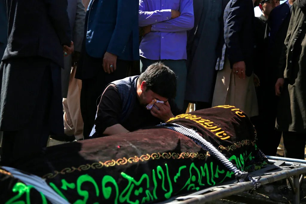 A man mourns over the body of a victim of deadly attacks on Saturday near a school in a cemetery west of Kabul, Afghanistan, May 9, 2021. The Interior Ministry announced the toll on Sunday the horrific bomb attack at the entrance to a girls' school in the Afghan capital has grown to around 50 people, many of whom were students between the ages of 11 and 15, and the number of injured during Saturday's attack also rose to over 100.