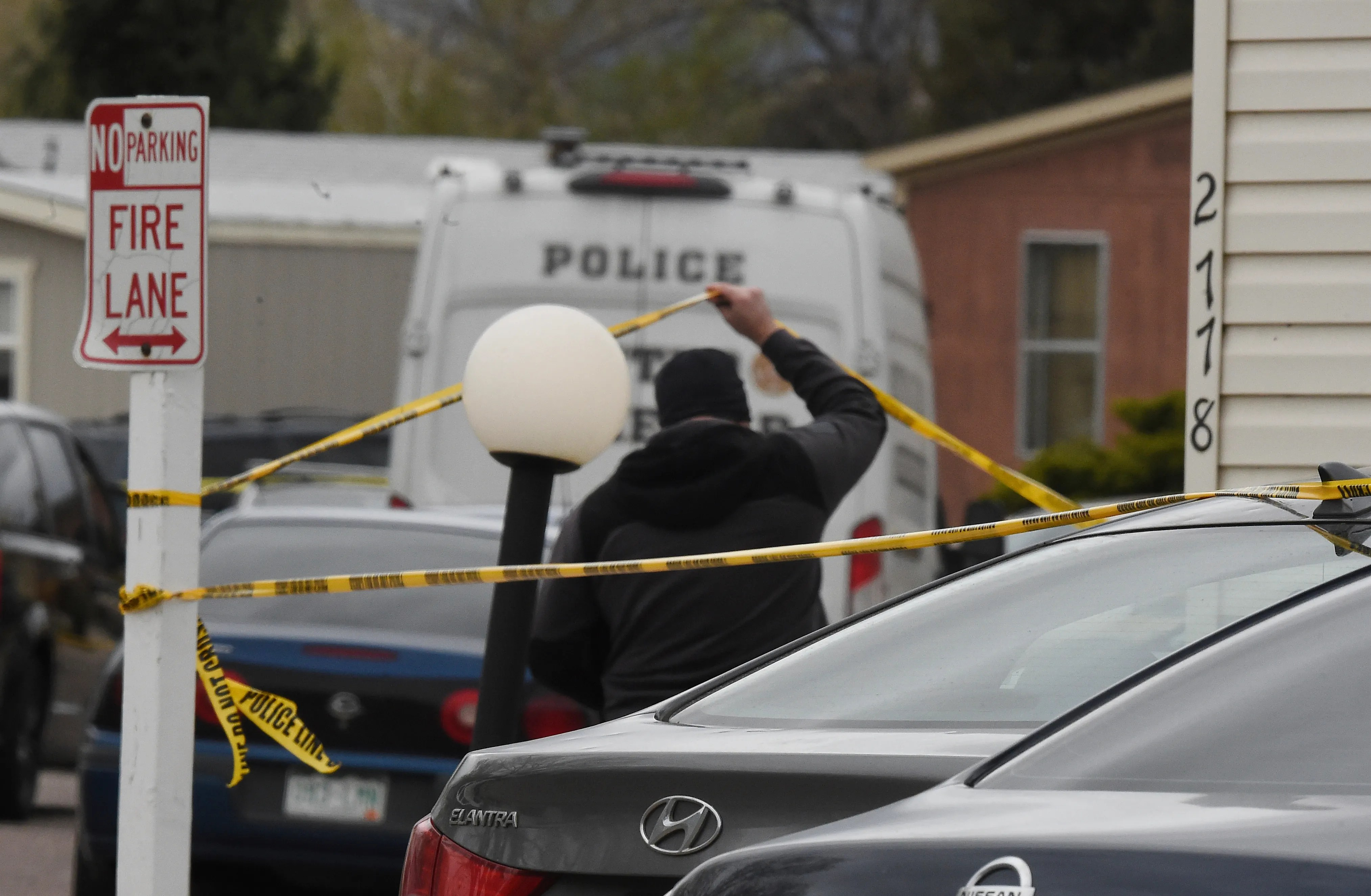 A Colorado Springs Police Department officer lifts up crime tape at the scene where multiple people were shot and killed early Sunday, May 9, 2021, in Colorado Springs, Colo.