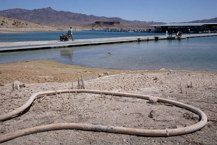 Barbaros Demircar hauls gear down to his boat at Temple Bar Marina on May 10, 2021, in the Lake Mead National Recreation Area, Arizona. The marina's waterline (ground) length is adjusted as water levels decline and the marina is moved out to deeper water.