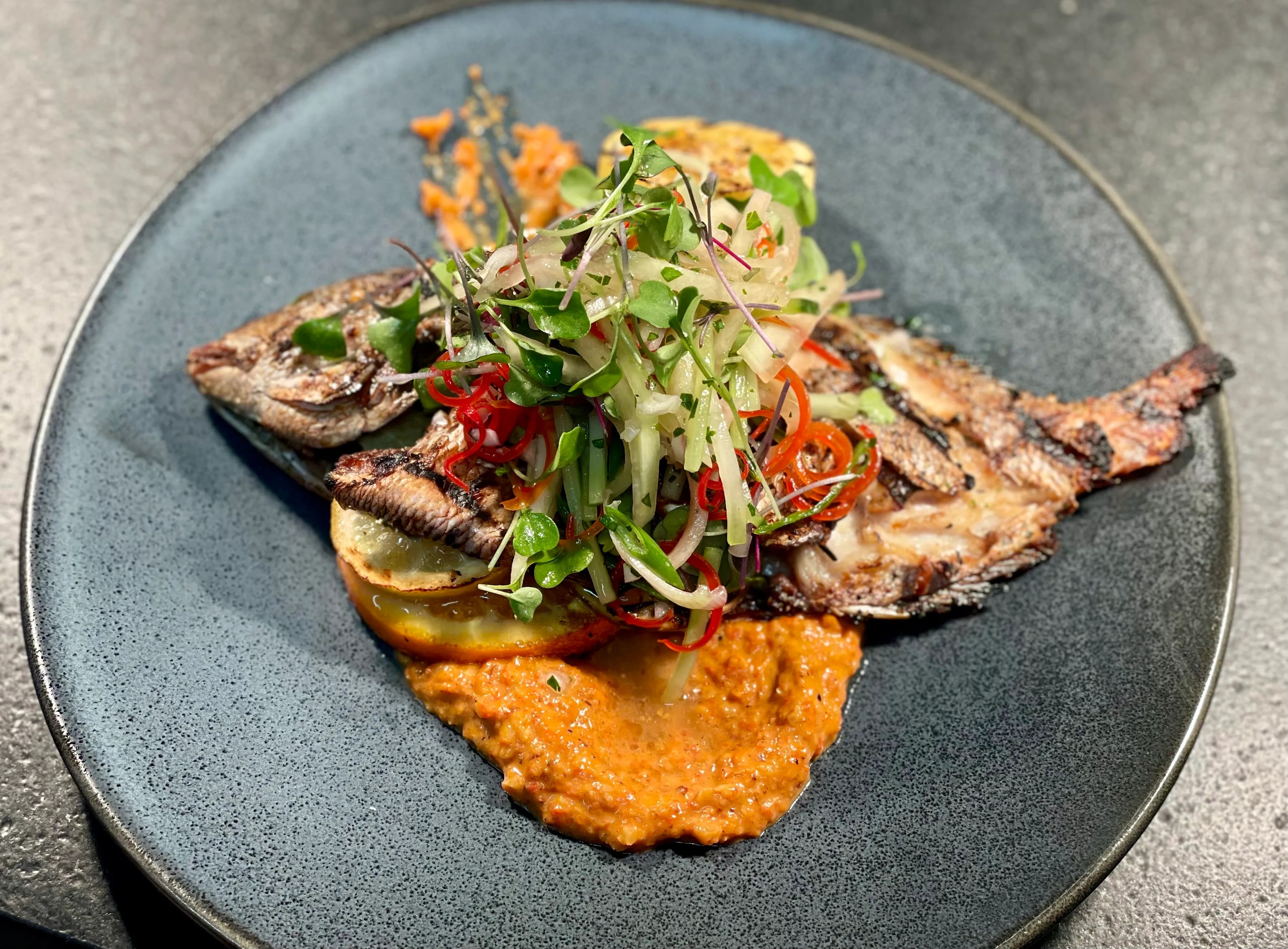 Core 450's whole grilled fish is chargrilled and stuffed with herbs and citrus and topped with a watermelon rind salad.