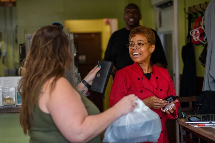 Stephanie Taylor, owner of Welcome Home Cafe smiles as she hands a takeout order to customer Lucy Berson on June 9, 2021 in Jenkintown, Pa.