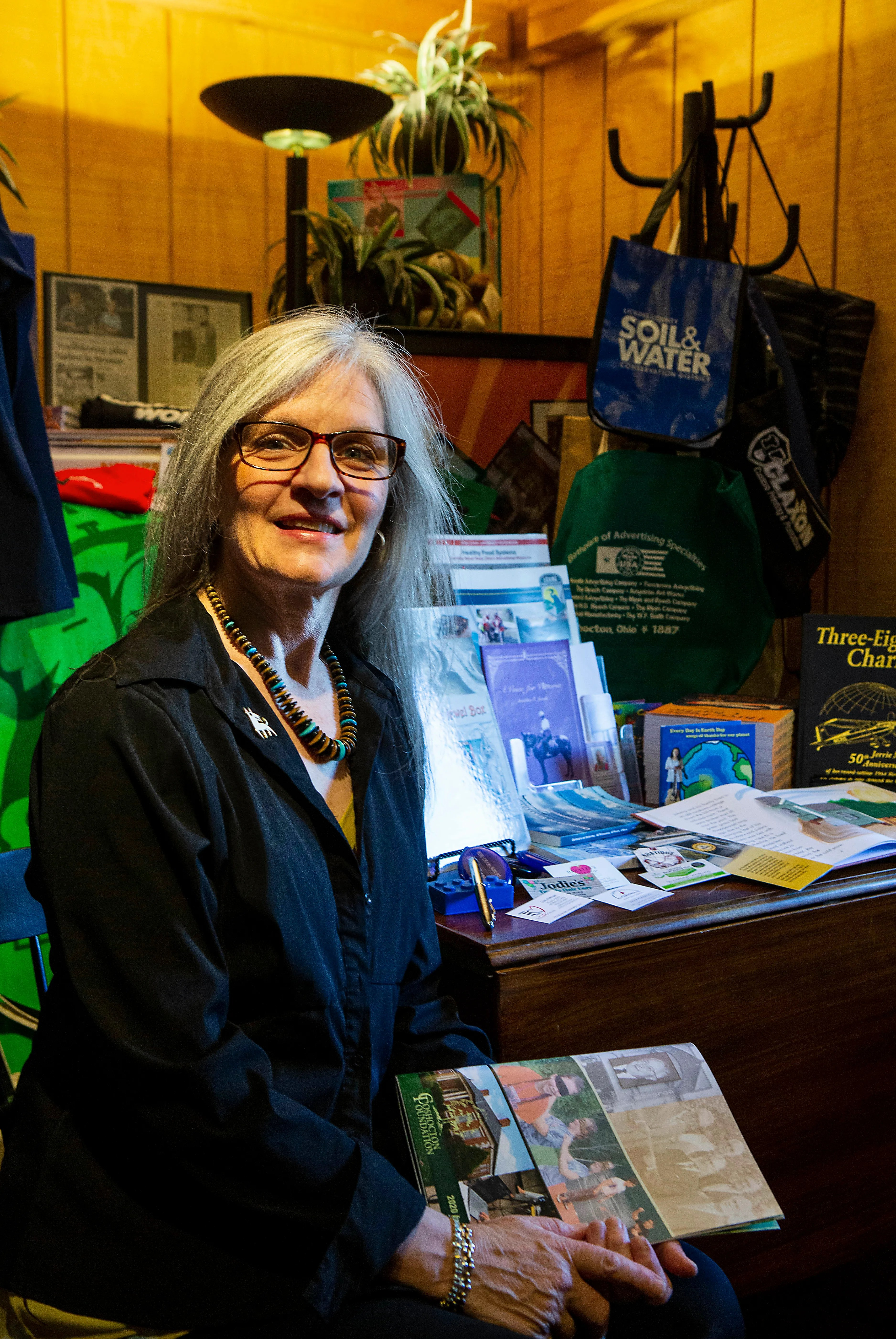 Wendy Hollinger, of Phoenix Graphix, sits by a some of the published books and other marketing and communications materials displayed at Phoenix Graphix in Granville, Ohio on June 14, 2021.
