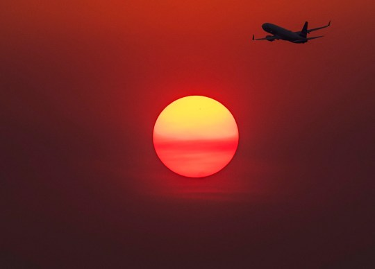 A plane flies near the sun as it glows red from smoke from the Telegraph Fire burning east of Phoenix June 15, 2021.The National Weather Service Phoenix AZ issued an excessive heat warning for portions of south central Arizona through the week.