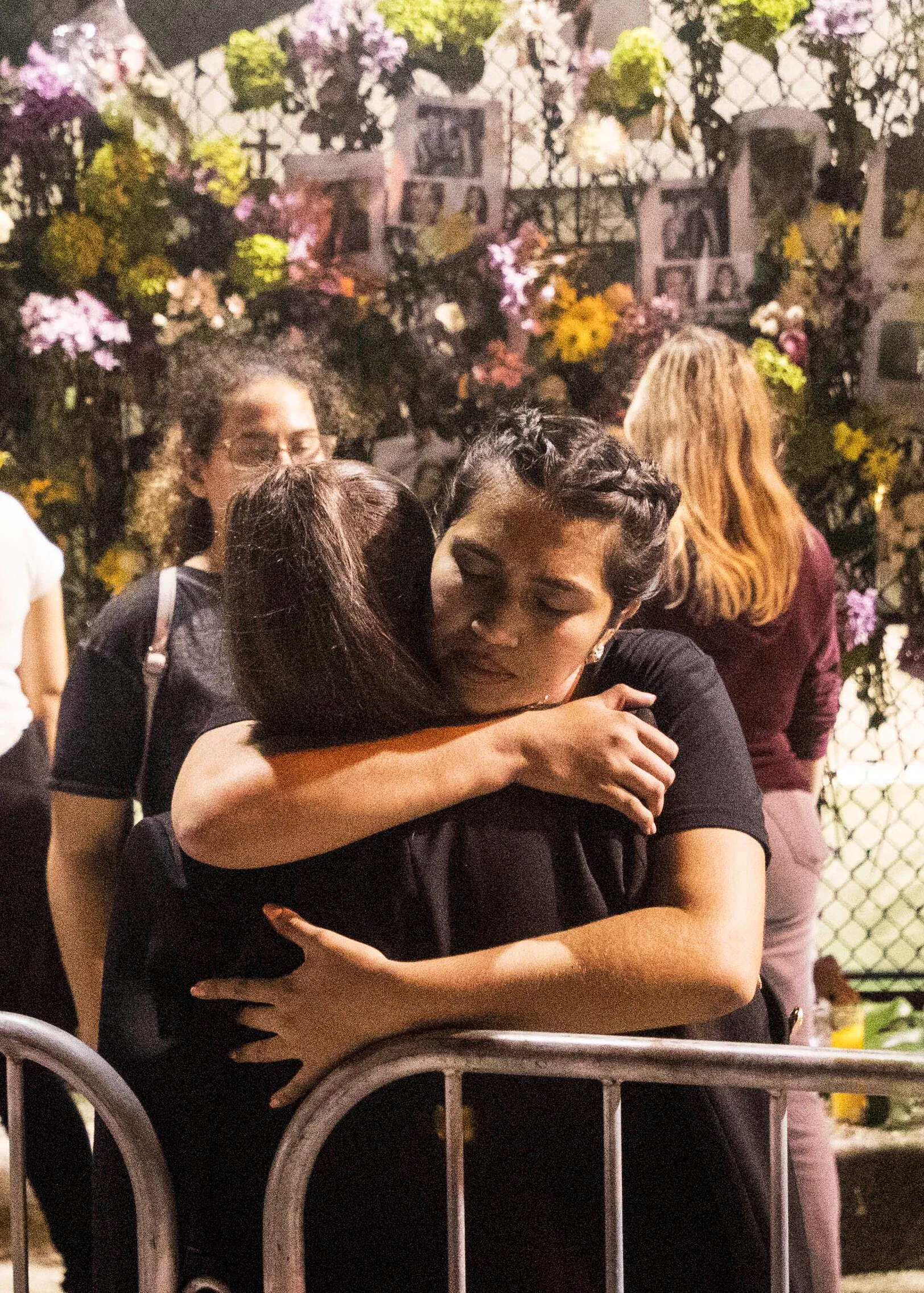 Florence Garcia hugs a woman at the memorial wall of those missing in the Champlain Towers collapse in Surfside, Fla., Monday, June 28, 2021.