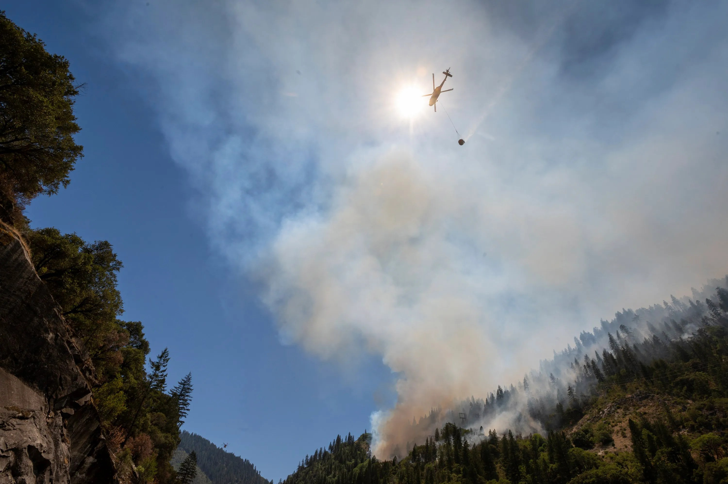 Helicopters drop water to battle the Dixie Fire on Highway 70 in the Feather River Canyon on Wednesday, July 14, 2021, in Plumas County. The Dixie Fire is burning in California's Butte and Plumas counties, not far from where the 2018 Camp Fire killed 85 people.