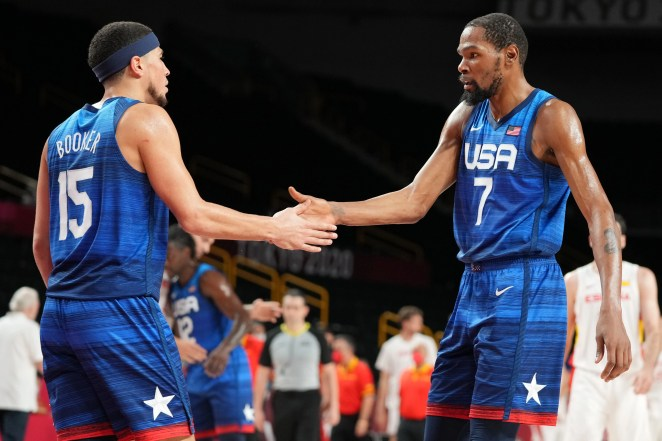 Devin Booker (15) and Kevin Durant congratulate each other after Team USA defeated Spain in an Olympic men's basketball quarterfinal game.