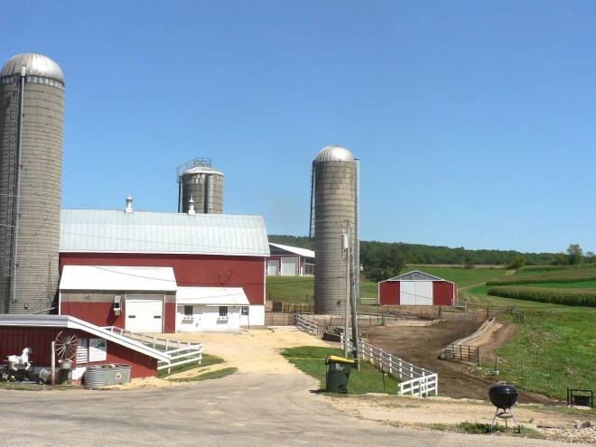 Red buildings and tall silos dominate the farmstead. The new calf barn is just left of the silo on the right. The machine shed is just right of that silo.