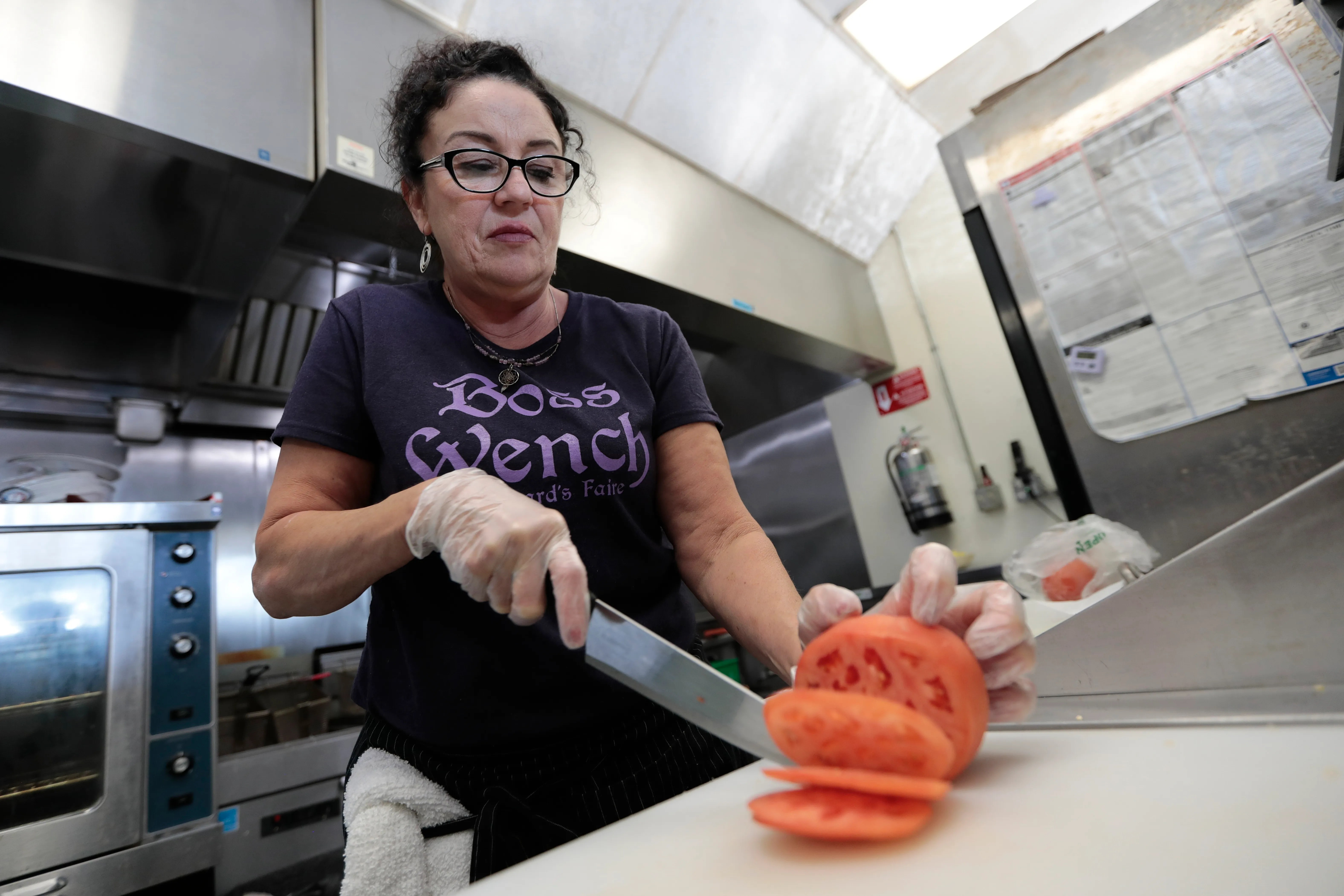 Deb DeSouza, owner, cuts a tomato for a breakfast sandwich at the Butternut Bistro on Acushnet Avenue in New Bedford.
